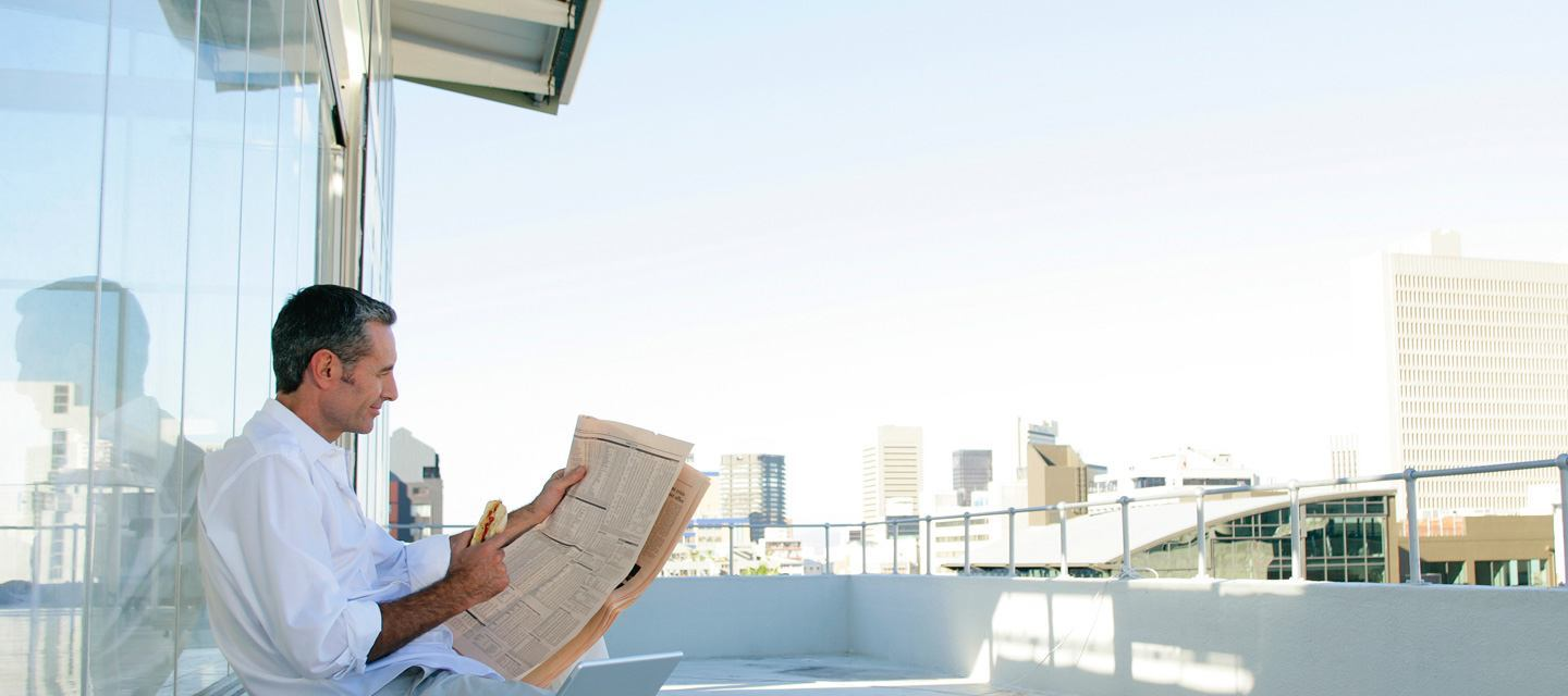 Man relaxing comfortably on a balcony over looking the city while reading the newspaper and eating a sandwich.